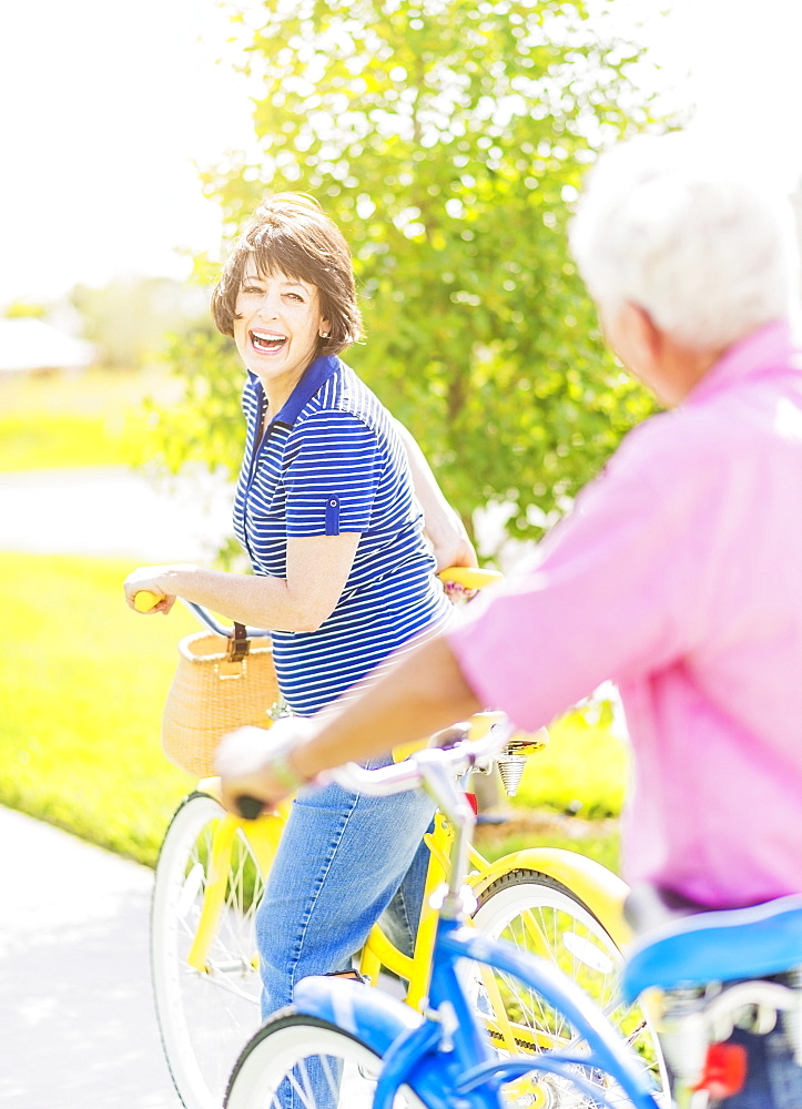 Portrait of woman looking over shoulder at senior man, while getting on bicycle and laughing, Jupiter, Florida