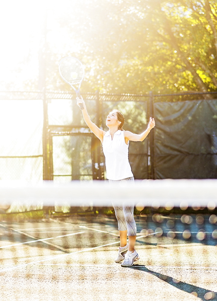 Young woman in tennis court about to serve ball with net in blurred foreground, Jupiter, Florida