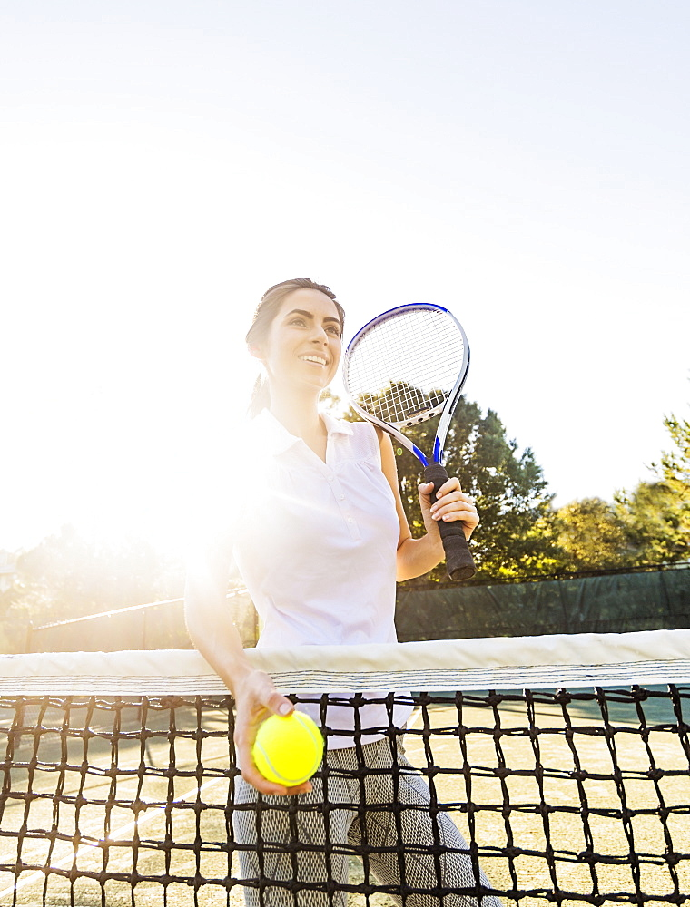 Portrait of young woman standing by net, holding tennis ball and tennis racket, Jupiter, Florida