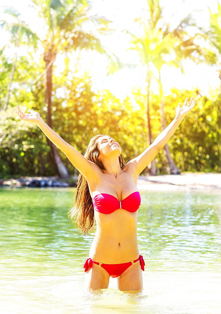 Portrait of young woman wearing bikini standing in waters of tropical lagoon, raising arms, Jupiter, Florida