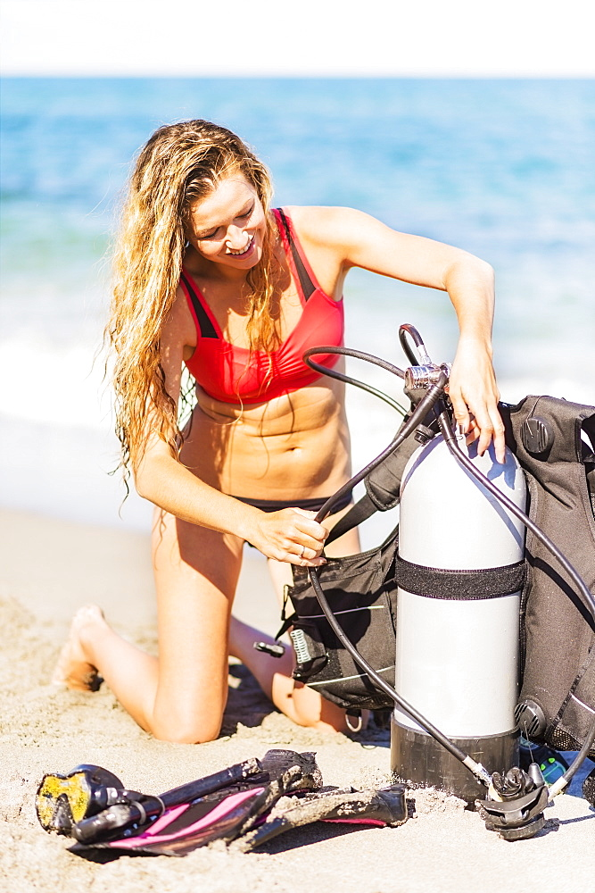Young woman kneeling on sandy beach putting together scuba diving equipment, Jupiter, Florida