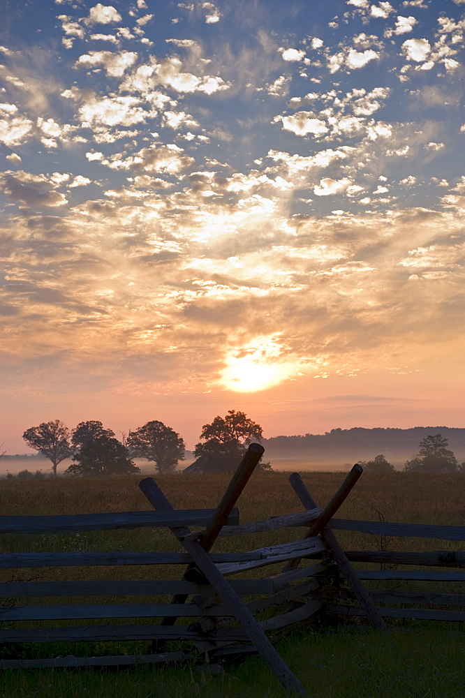 Sunrise over rustic fence