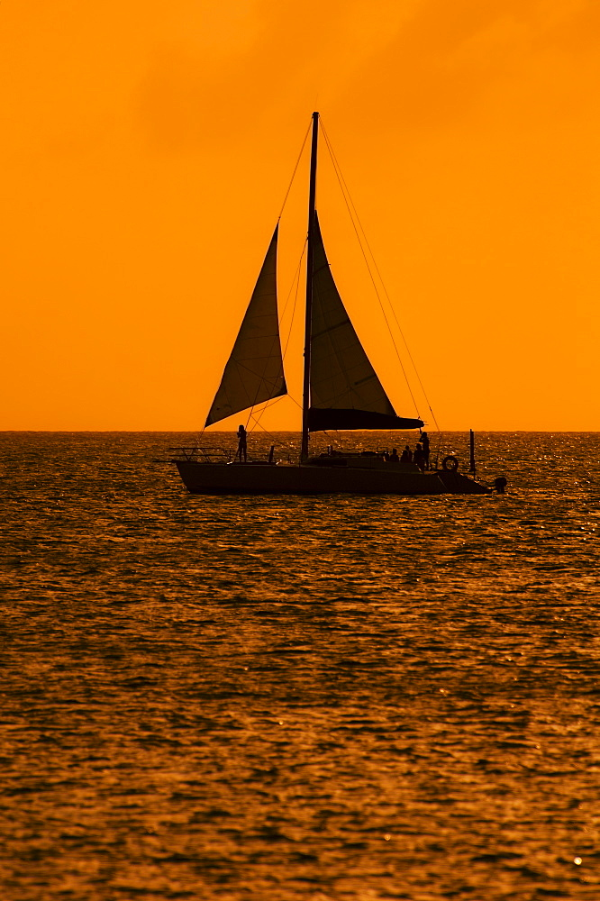 Silhouette of sailboat at sunset