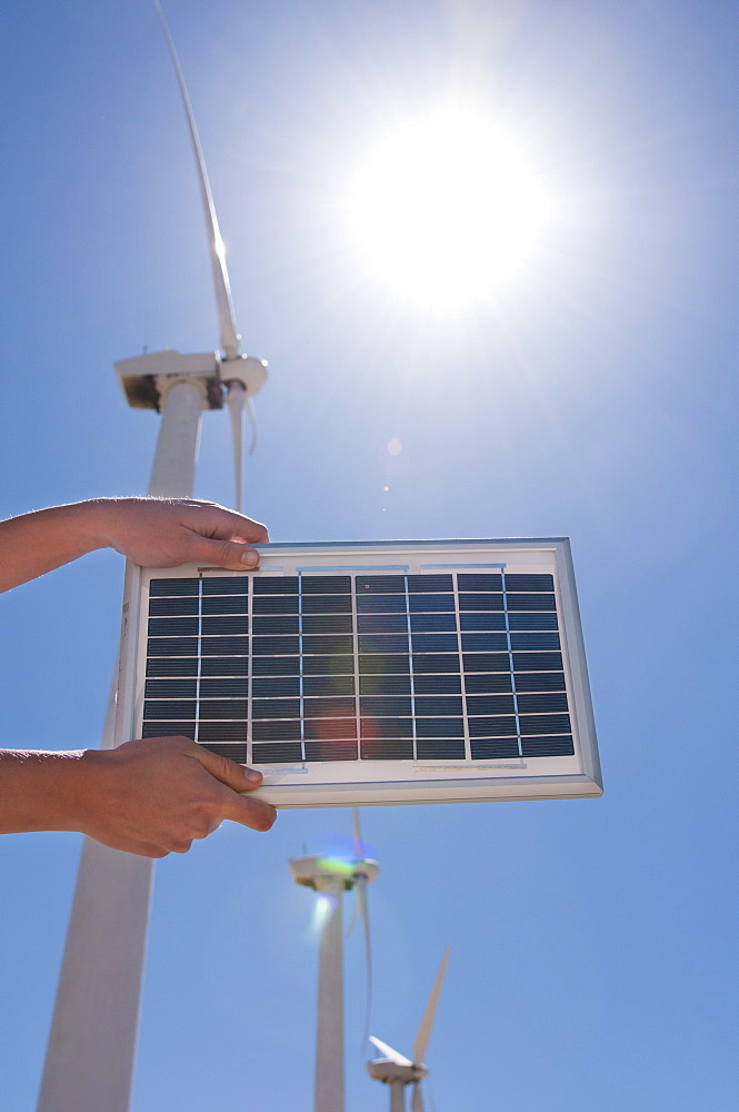 USA, California, Palm Springs, Woman's hands holding solar panel with wind turbines