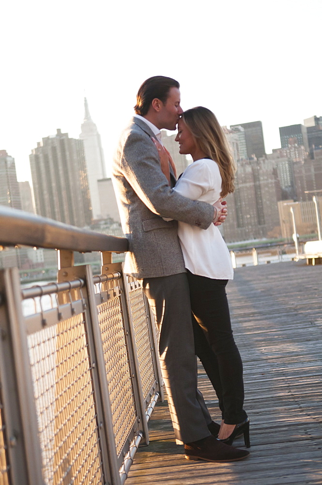 USA, New York, Long Island City, Young couple kissing on boardwalk, Manhattan skyline in background