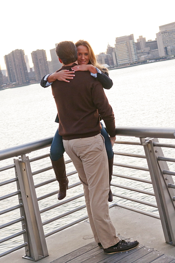 USA, New York, Long Island City, Young couple embracing on boardwalk