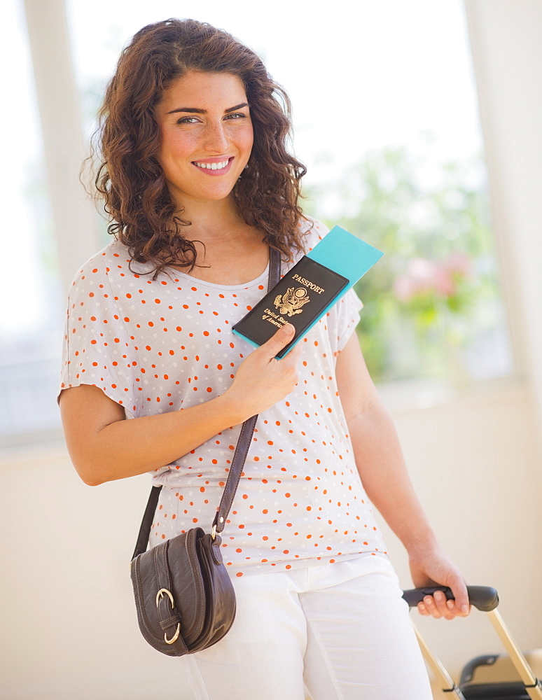 Smiling woman with luggage and passport