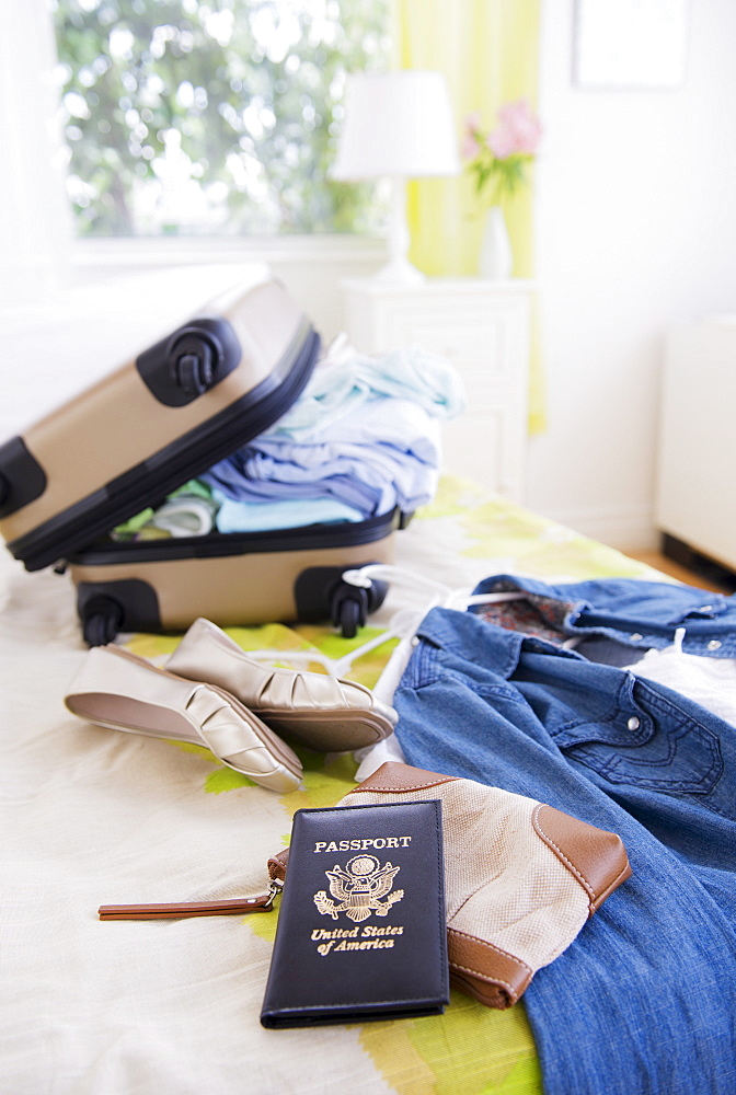 Suitcase and passport on bed during packing