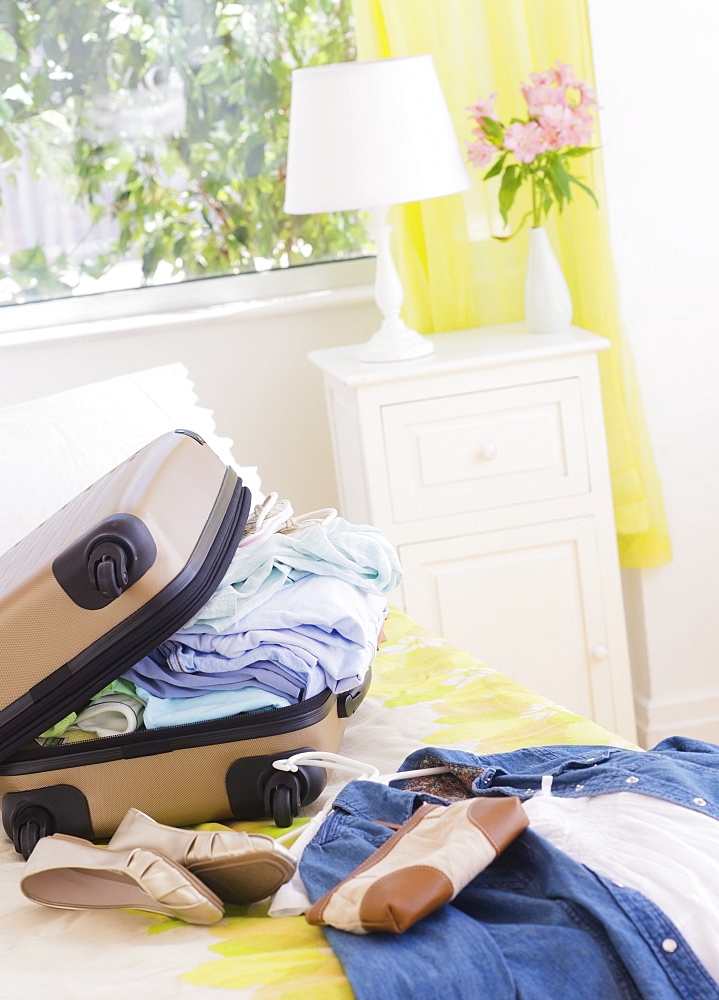 Suitcase on bed during packing