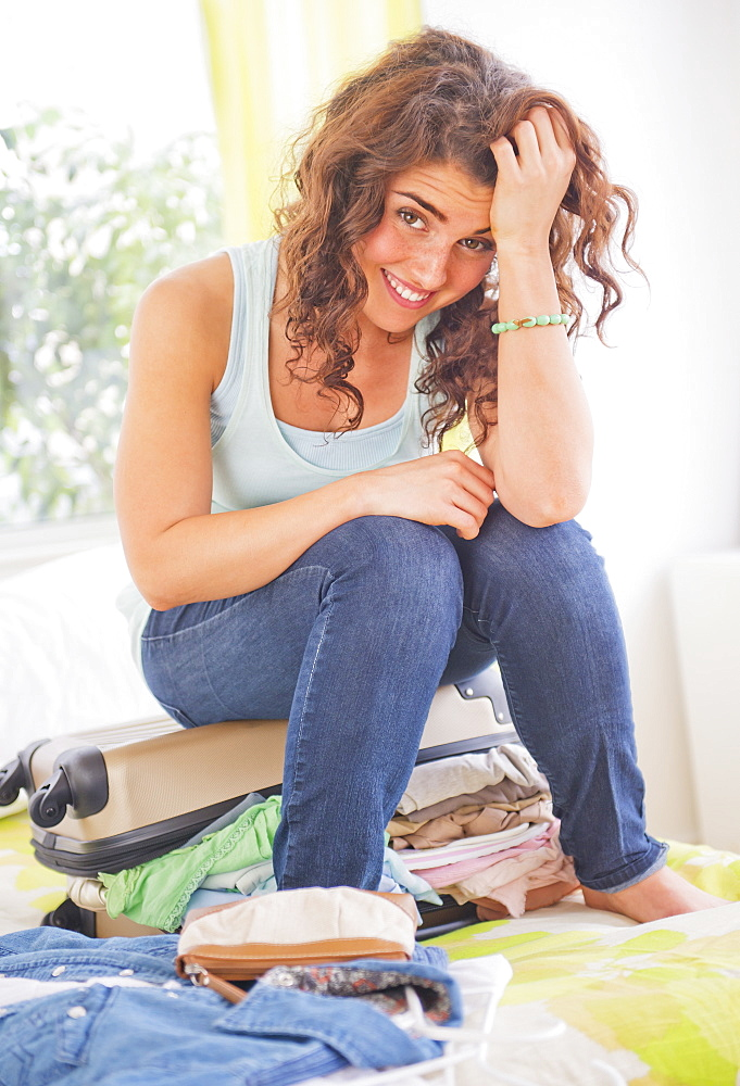 Woman sitting on suitcase full of clothes