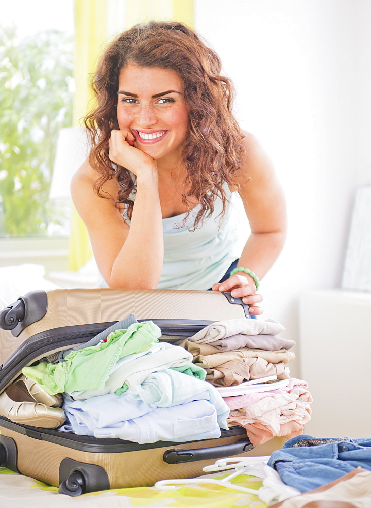 Smiling woman packing suitcase
