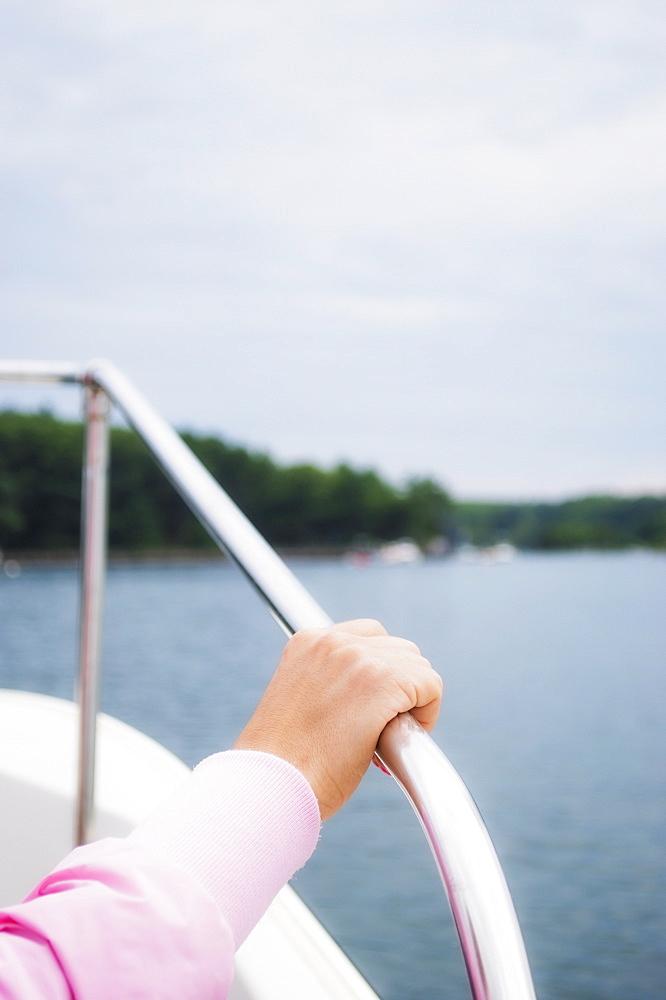 Hand holding yacht railing, USA, New Hampshire, Portsmouth