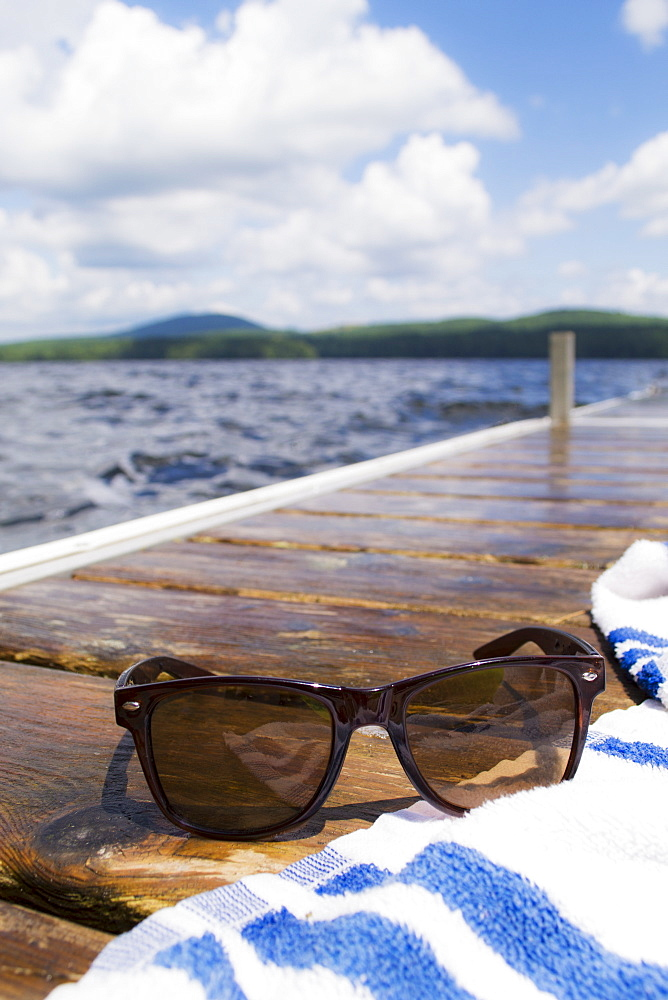 Close-up of sunglasses and towel on jetty, USA, Maine, Camden