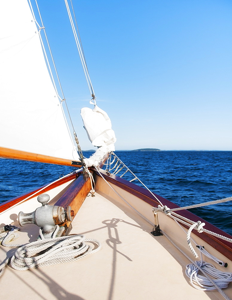 View of sea with yacht bow and sail in foreground, USA, Maine, Camden
