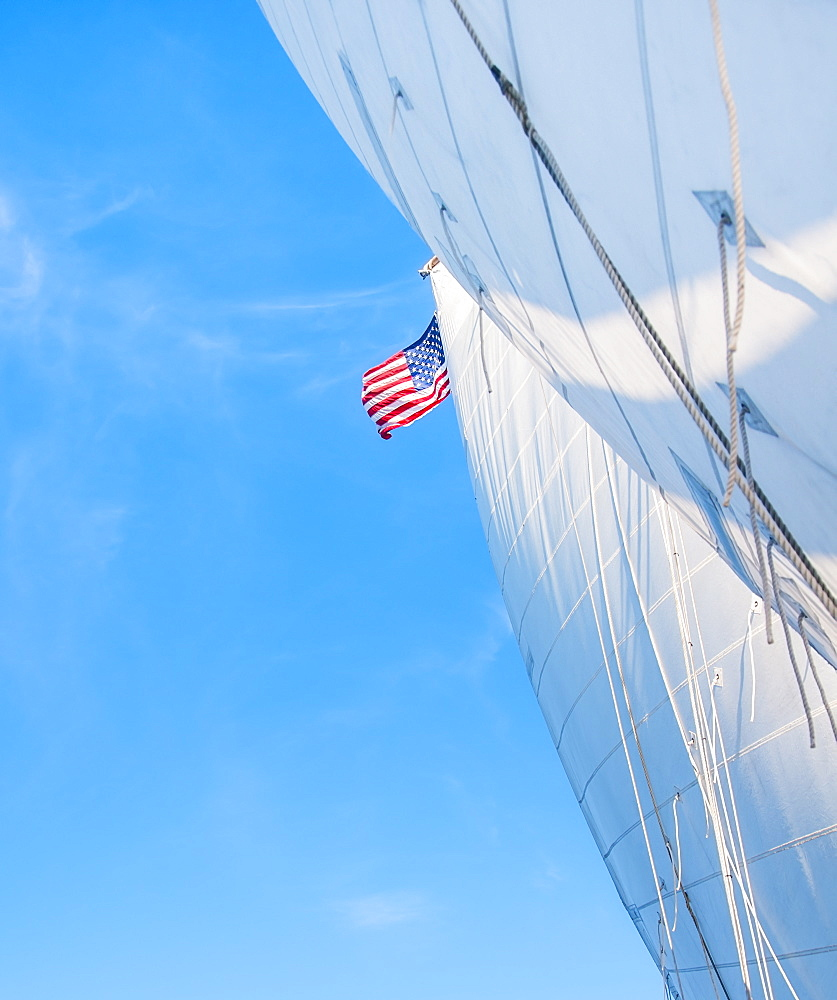 White sails and American flag against blue sky, USA, Maine, Camden