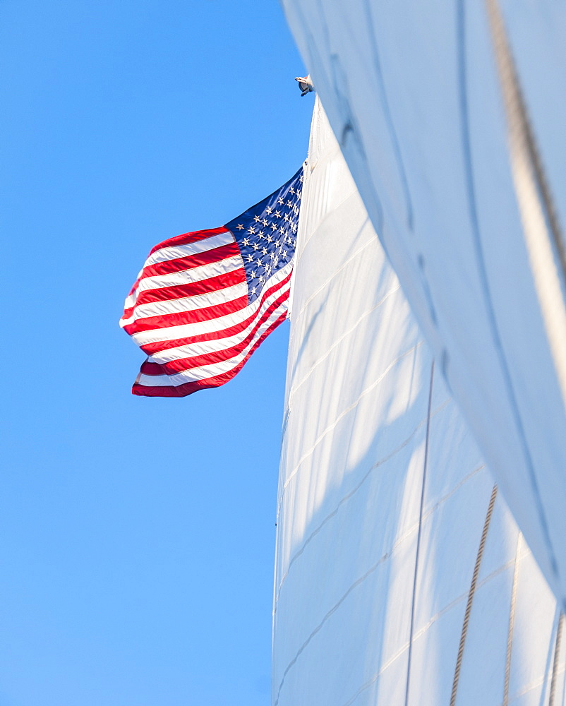 White sails and American flag against blue sky