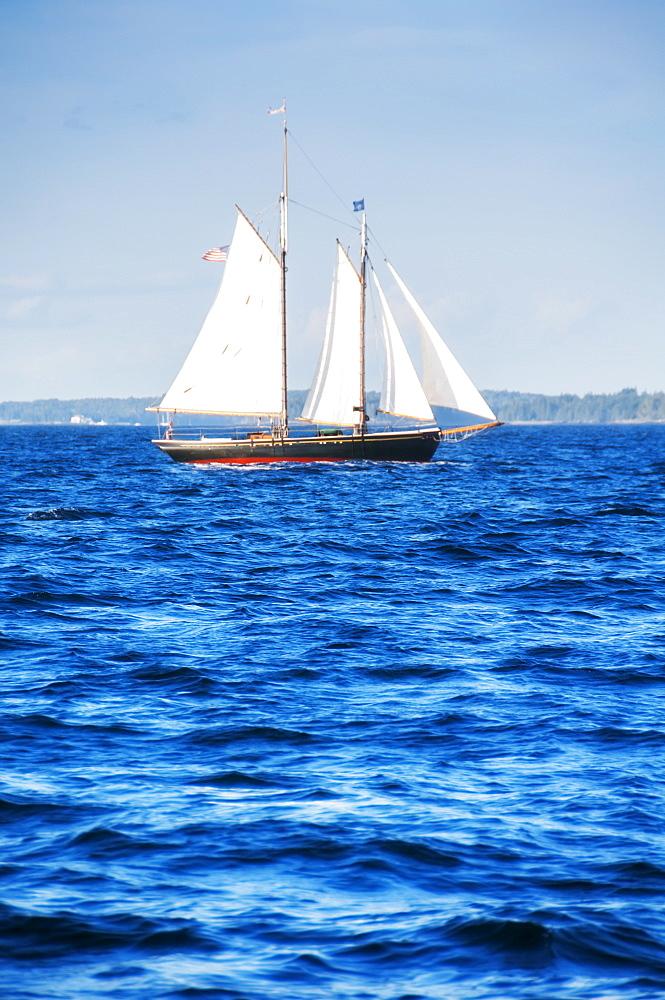 Small yacht sailing on blue sea