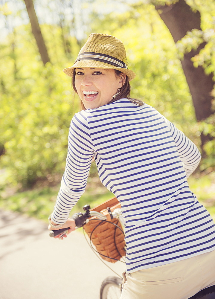 Portrait of mid adult woman riding bicycle, Central Park, New York City