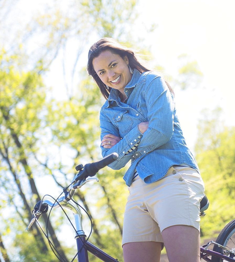 Portrait of mid adult woman with bicycle, Central Park, New York City