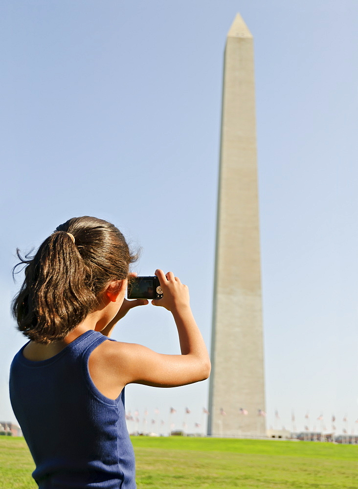 USA, Washington DC, girl (6-7) photographing Washington Monument
