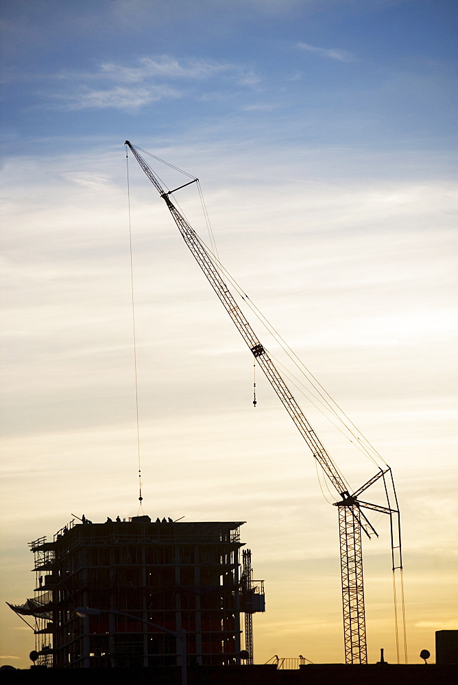 Crane and urban construction site at dusk