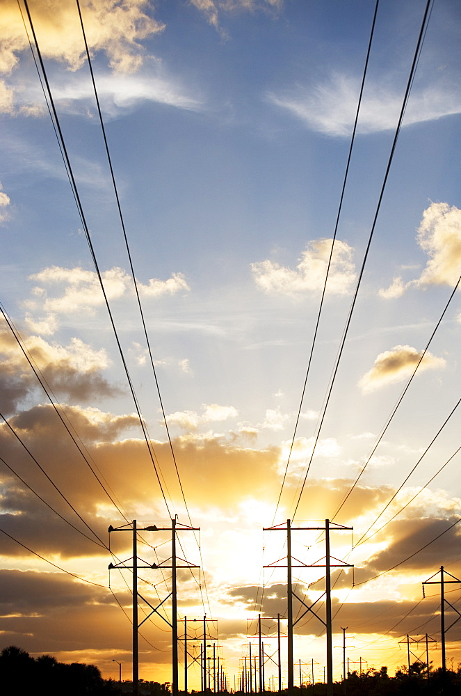 Electrical poles and wires at sunset