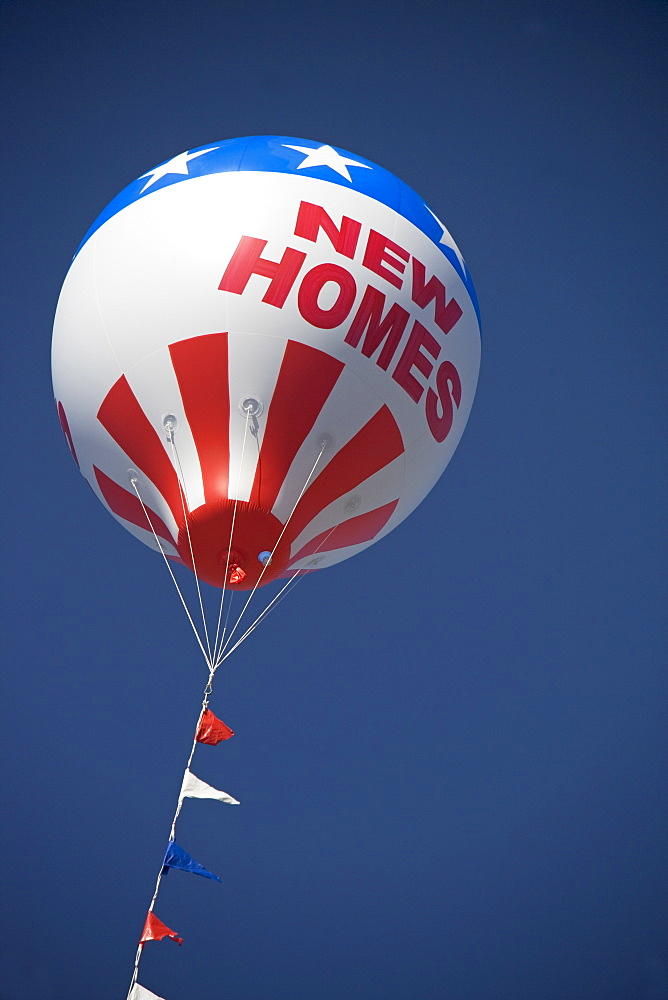 A large promotional balloon that says New Homes