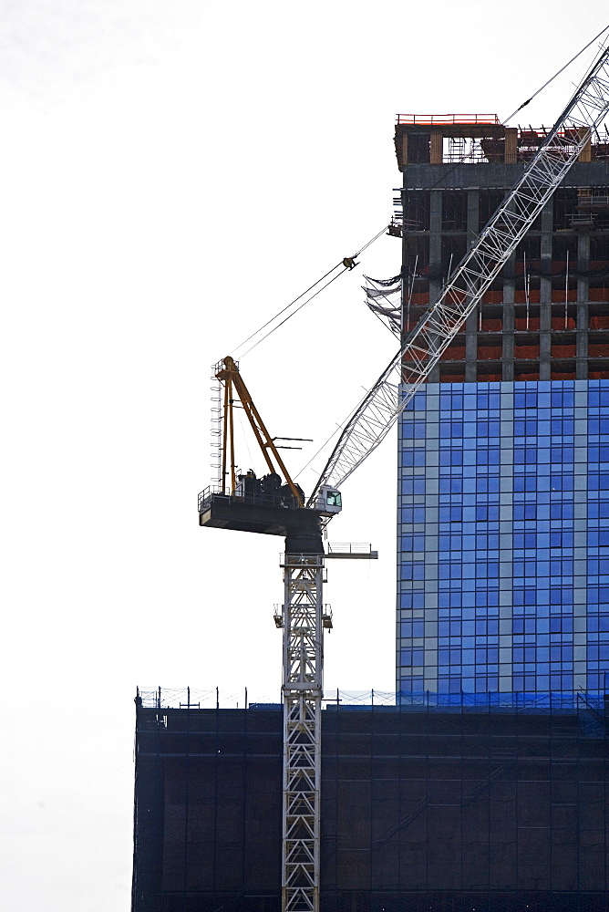 Crane beside high-rise building