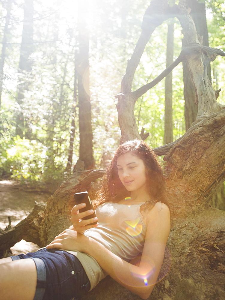 Young woman sitting on log and text messaging, USA, Oregon, Portland