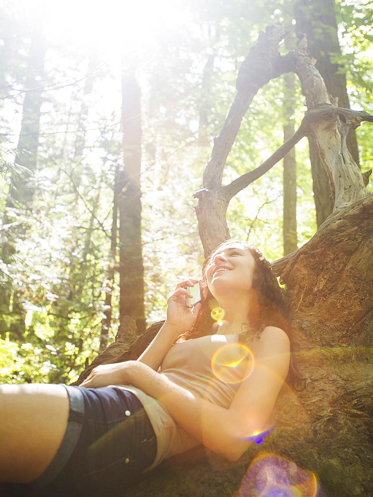 Young woman sitting on log and using cell phone, USA, Oregon, Portland