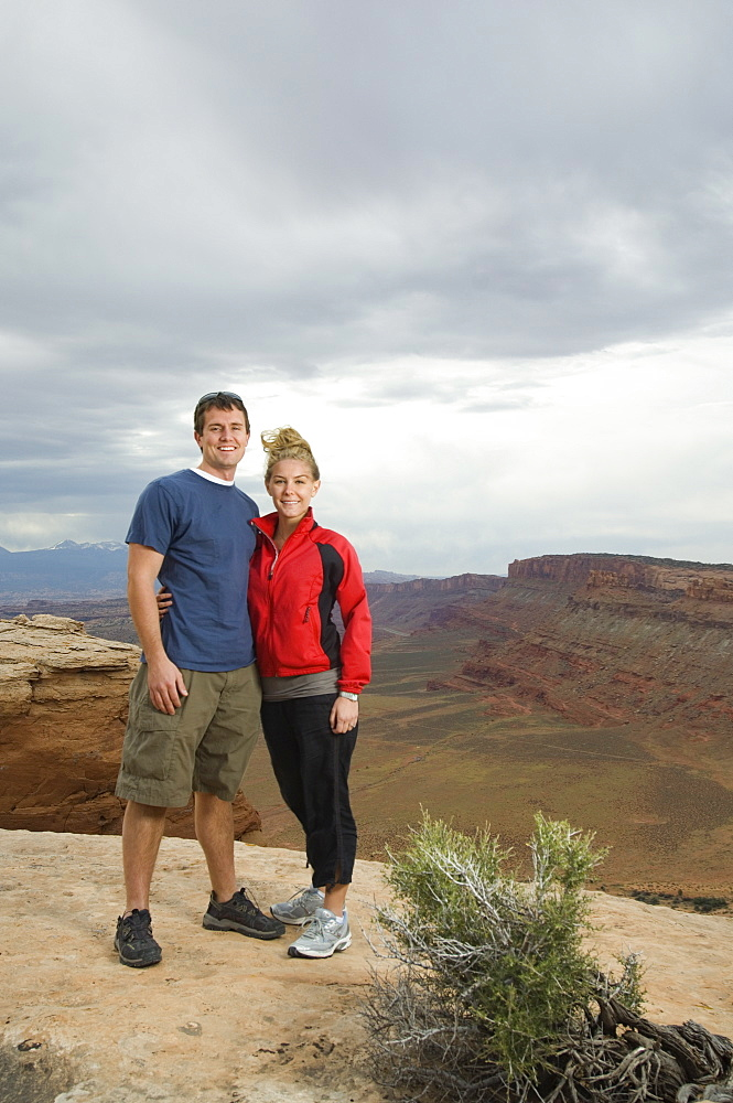 Couple standing at edge of cliff