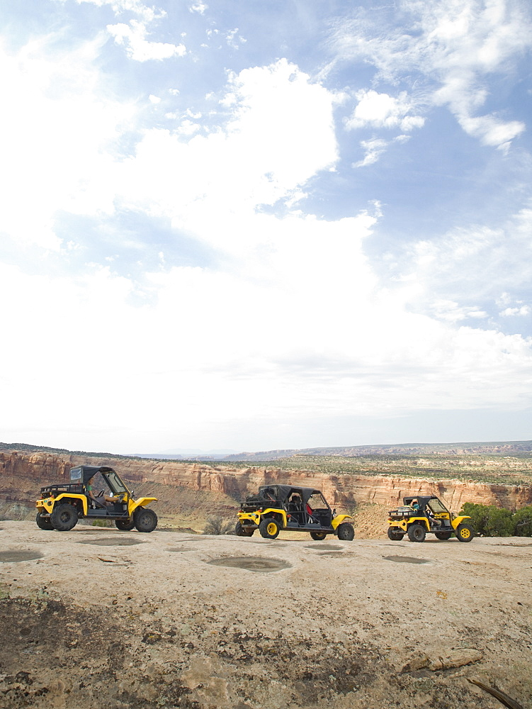 People in off-road vehicles on rock formation