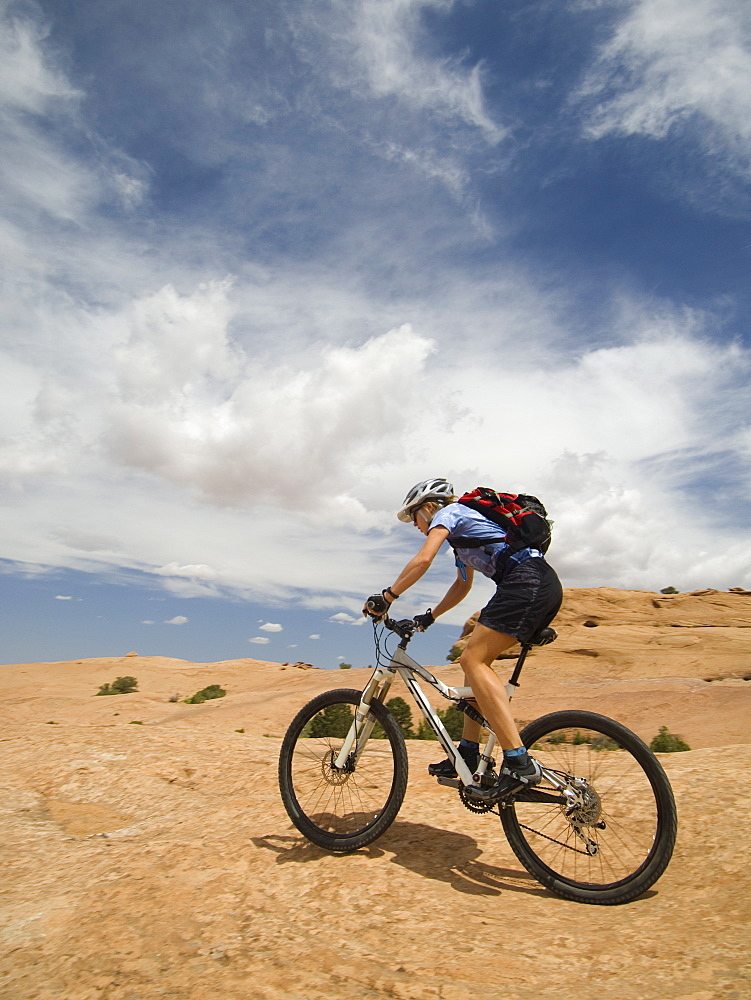 Woman riding mountain bike in desert