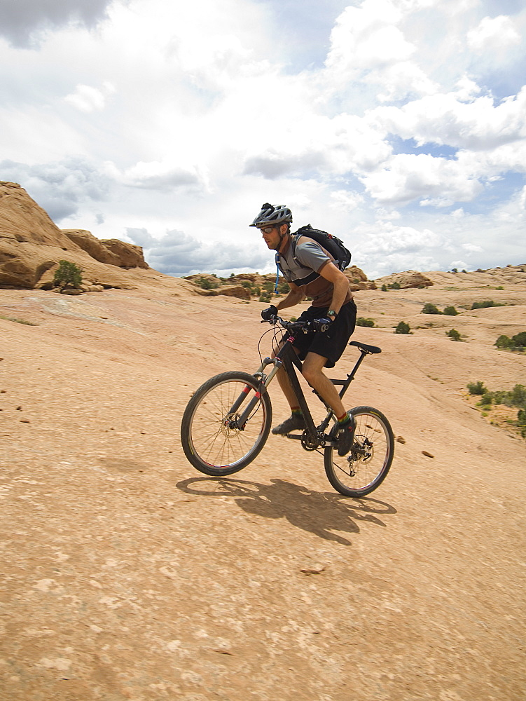 Man riding mountain bike on rock formation