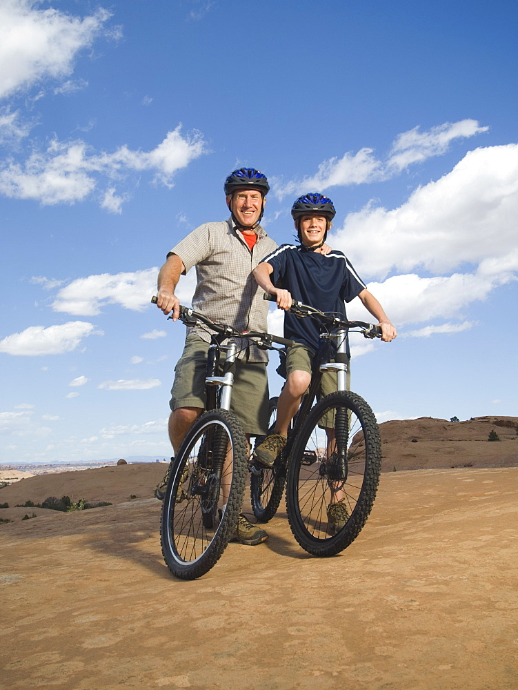 Portrait of father and son on mountain bikes