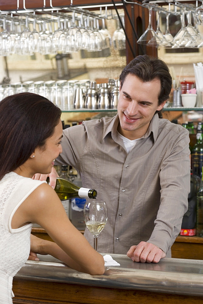 Male bartender pouring wine for female customer