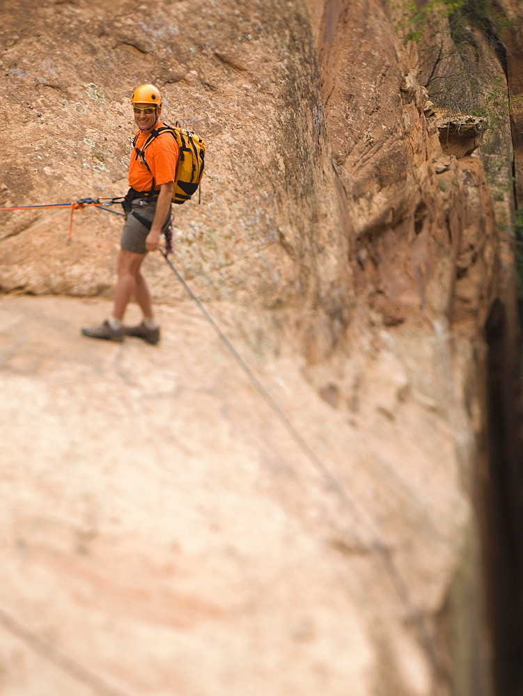 Man in rappelling gear at top of cliff