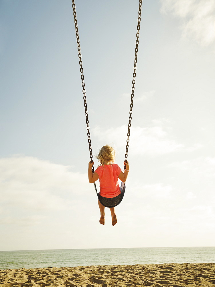 Girl (4-5) swinging on beach, San Clemente, California