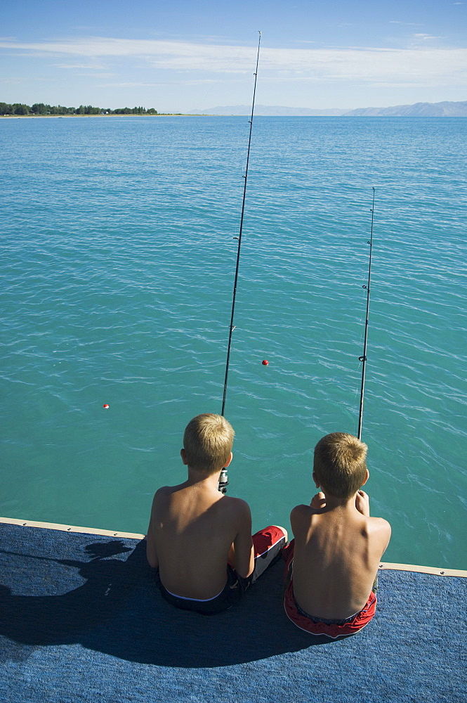 Brothers fishing off dock in lake, Utah, United States