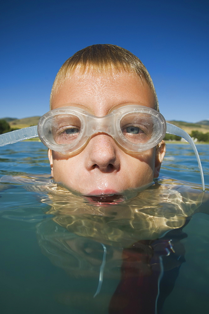 Boy wearing swimming goggles in water, Utah, United States