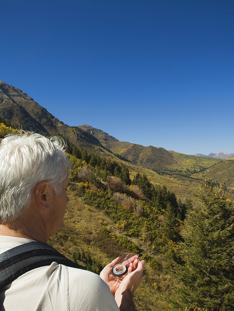 Senior man holding compass, Utah, United States
