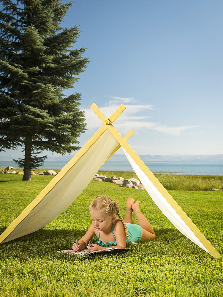 Girl (2-3) lying in tent, Garden City, Utah
