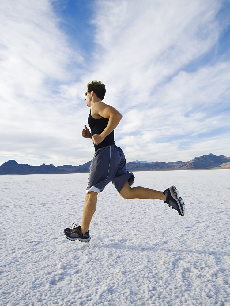 Man running on salt flats, Utah, United States