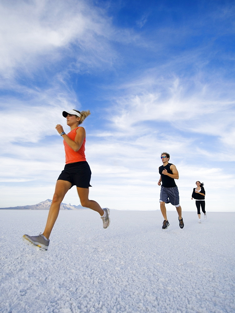 People running on salt flats, Utah, United States
