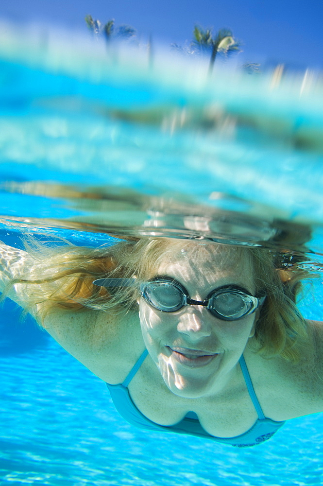Woman wearing goggles underwater