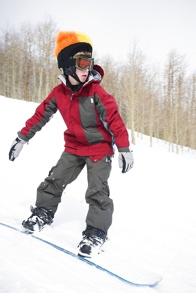 Boy snowboarding downhill