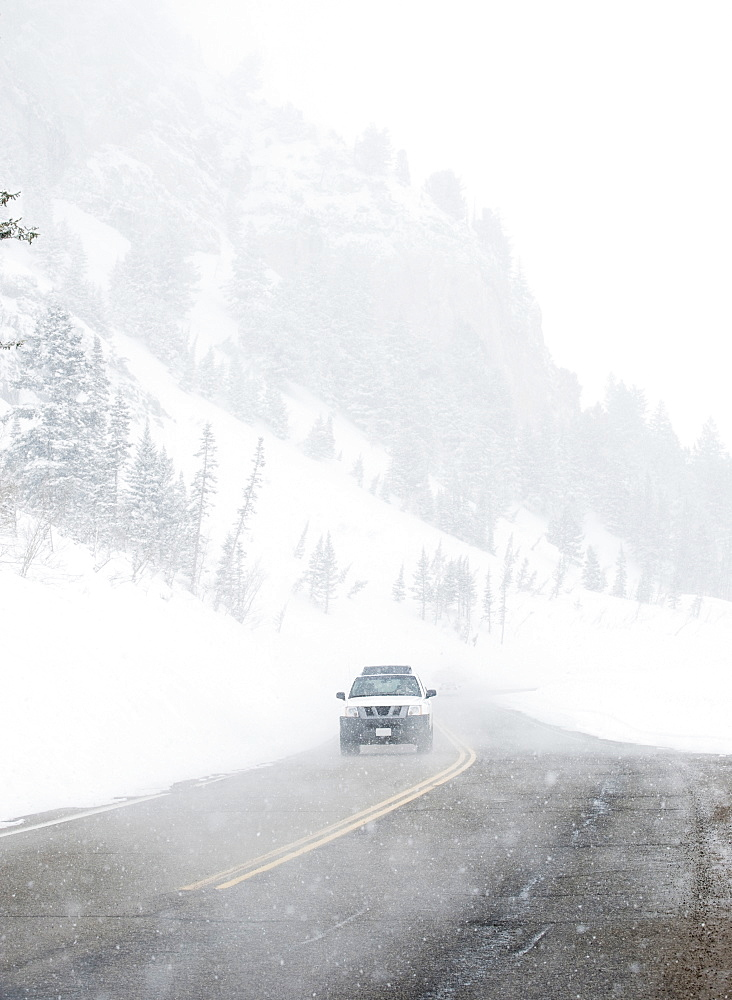 Car driving on snow road, Wasatch Mountains, Utah, United States