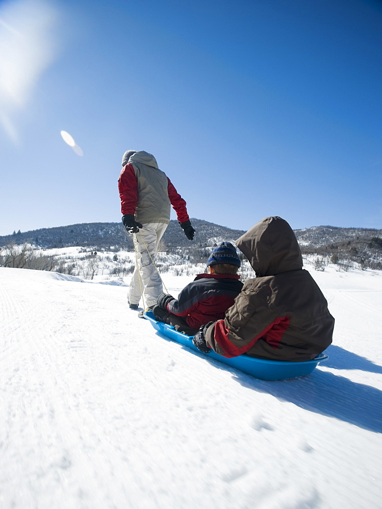 Father pulling children on sled