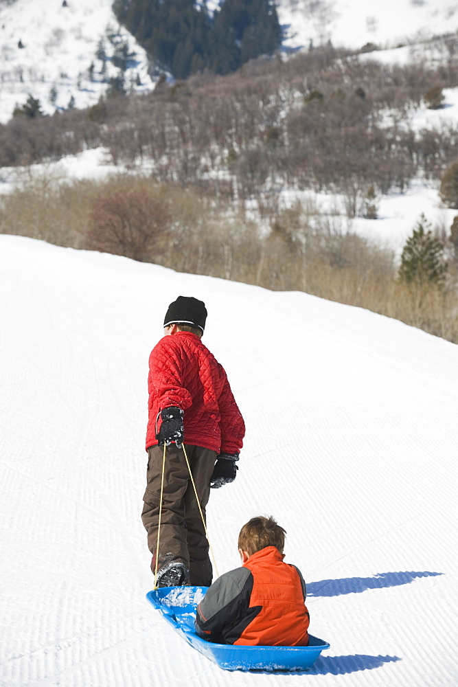 Boy pulling brother in sled