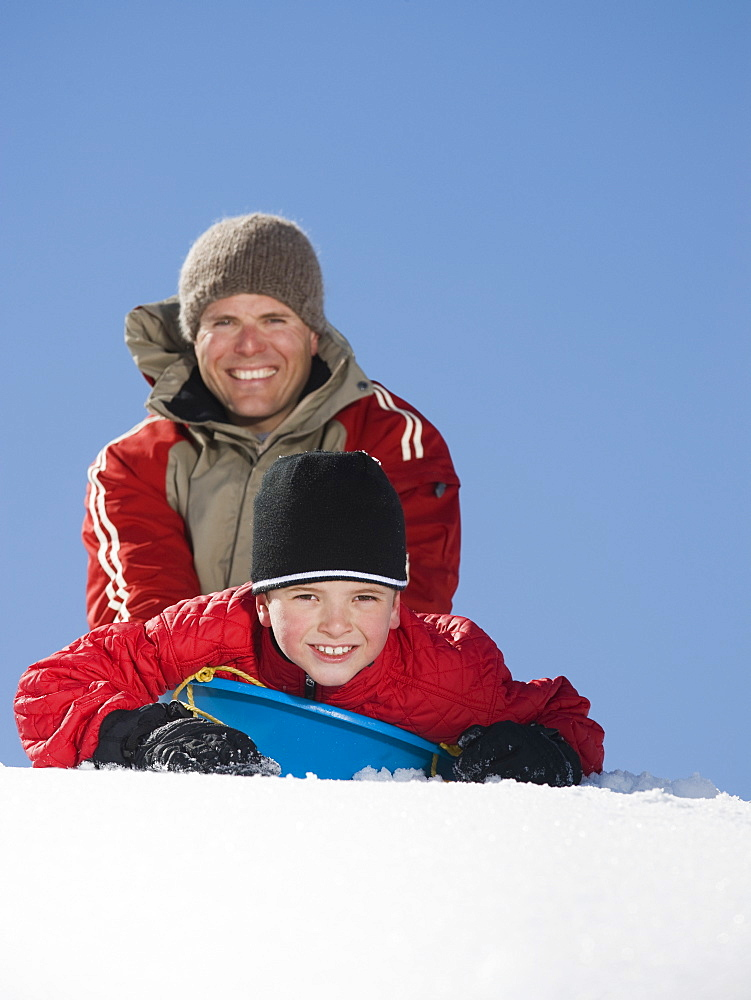 Father and son on sled in snow